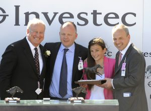 Lee, Eve and Martin Taylor collect Dancing Rain's Oaks trophy from Bernard Kantor of Investec, left